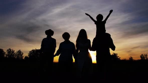 Three Generation Family Walking at Bright Sunset