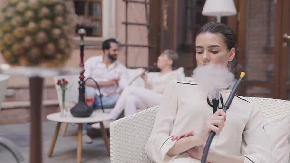 Hookah Lounge. Beautiful Woman Smoking Pineapple Shisha