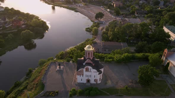 Thumbnail for Small Church at the Bank of the River at the Summer Sunset Filmed By Drone in Small European City
