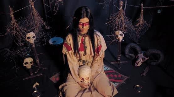 Thumbnail for Junge Ureinwohner American Woman sitzt auf dem Boden unter den Schädeln