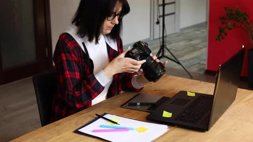 Photographer Female Working in a Creative Office Holding Camera at Desk and Retouch Photo