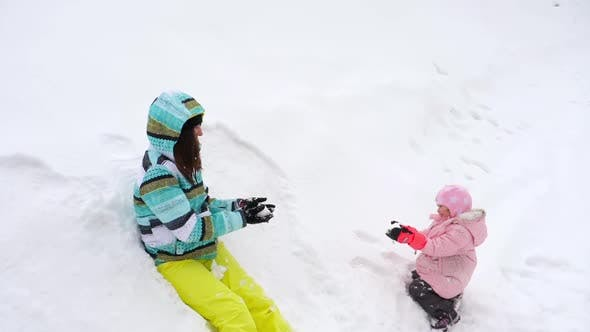 Cover Image for Mom with a Three-year-old Daughter Play Snowballs