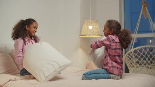 Black Preadolescent Sisters Pillow Fighting on Bed