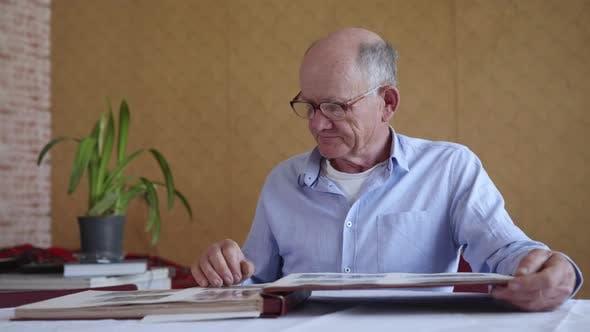 Thumbnail for Cheerful Elderly Man Enjoying Memory of Family Photo Album, Watching Old Photos