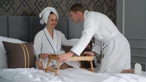 Un homme apporte le petit déjeuner à sa femme dans un lit