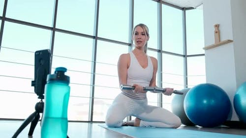 Young sporty girl showing exercises online using smartphone