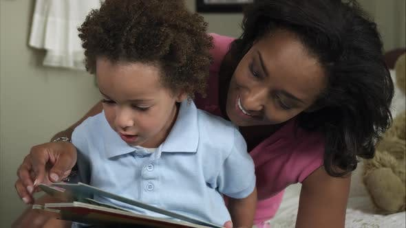 Thumbnail for Slow motion of mother cuddling young boy reading book