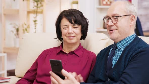 Thumbnail for Happy Senior Couple Having a Video Call Seated on Couch in Their Living Room