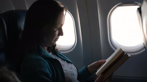 Female Passenger of Airplane Reading Book