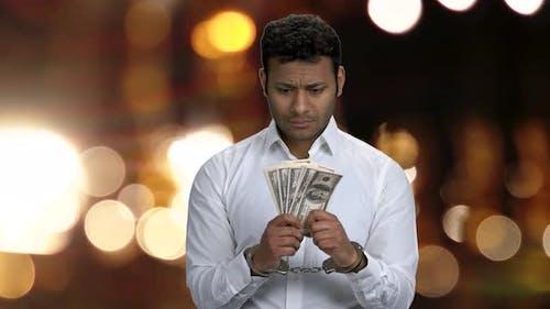 Handschellen gefesselter Geschäftsmann mit Dollarnoten.