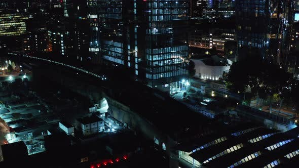 Aerial Night View of Train Arriving Into Station in Between Tall Buildings Modern District