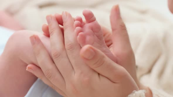 Closeup Shot of Young Mother Gently Holding and Touching Little Feet of Her Newborn Baby Boy Lying
