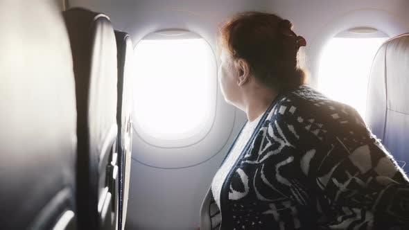 Senior European Female Airplane Passenger Sitting on the Airplane Window Seat, Nervous and Scared