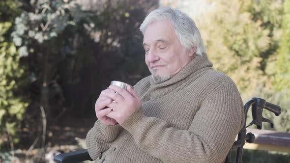 Thumbnail for Seitenansicht Porträt älterer kaukasischer Mann trinken heißen Tee als sitzen im Rollstuhl im Freien