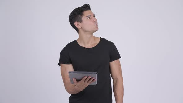Thumbnail for Happy Young Handsome Multi-ethnic Man Thinking While Using Digital Tablet