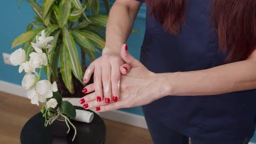 Woman Applying Lotion on Hand Moisturizing Skin with Daily Cream
