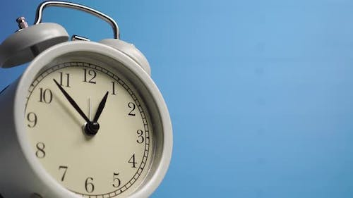 Movement of the hour and minute hands of an analog gray alarm clock