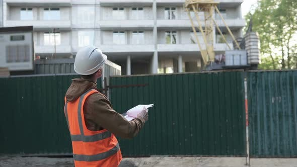 Thumbnail for A High-Level Builder at a Construction Site Monitors Work
