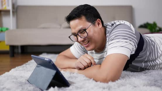 Young father laying on carpet and video call on tablet