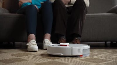 Robotic Vacuum Cleaning While Old Couple Relaxing