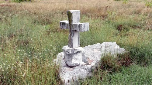 Stone cross as a tombstone of an old tomb in a grassy field. A single grave surrounded by grass.