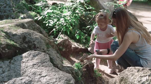 Thumbnail for Young Beautiful Mother with Her Daughter Feeding a Chipmunk in the Woods, Among Stones
