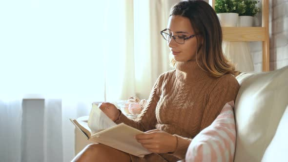 Thumbnail for Beautiful Young Woman Sits On Sofa In Room And Reads Book