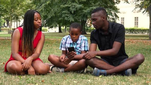 Thumbnail for A Black Family Sits on Grass in a Park and Works on a Smartphone