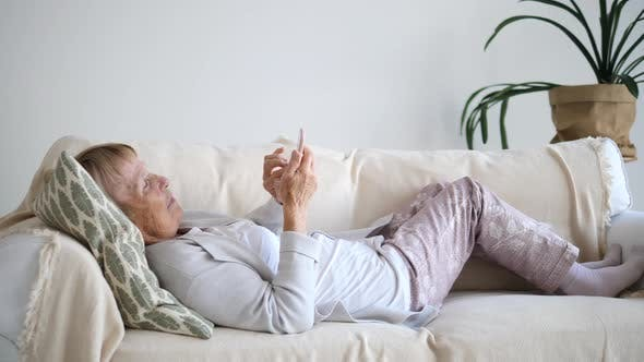 Senior People And Technology Concept. Grandmother Lying On Sofa With Cell Phone.