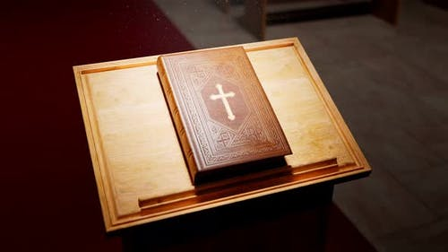 Holy Bible on a wooden table lightened by rays of light falling in the chapel.