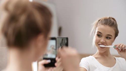 Schöne kaukasische Mädchen nehmen selfies mit Zahnbürste vor Spiegel