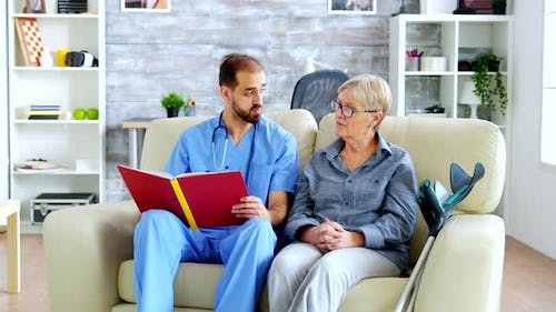 Male Assistant in Nursing Home Reading a Book To Retired Elderly Pensioner
