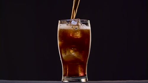 Pepsi Foam in the Glass Forming Cycle on a Black Background