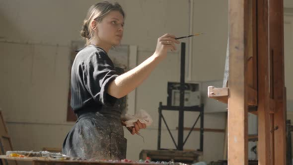 Thumbnail for Woman in Dirty Apron Draws Picture on Canvas Put on Easel