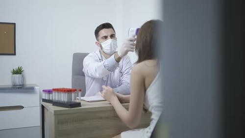 Doctor wearing protective mask use infrared forehead thermometer to check patient body temperature.