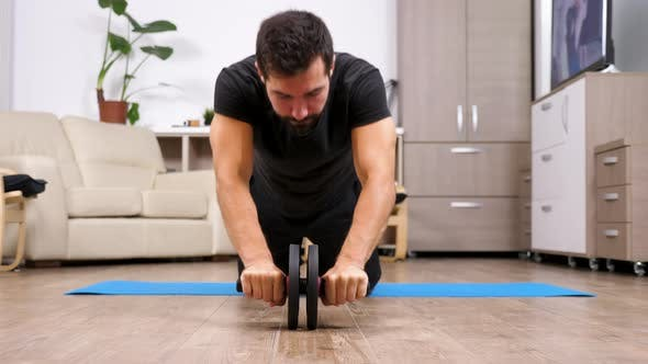 Thumbnail for Sport at Home - Fit Man Doing Exercises with an Ab Whell