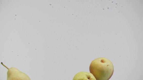 Cover Image for Fresh Fruits Red and Yellow Pears Falling Into Water with Splash and Air Bubbles White Background