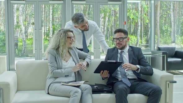 Cover Image for Cheerful Businesspeople Discussing Information on Clipboard