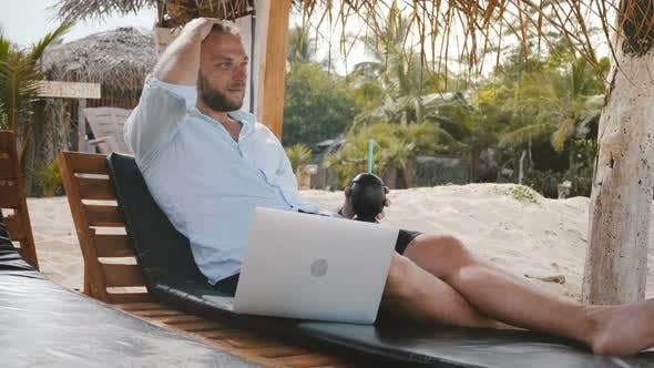 Thumbnail for Successful Happy Relaxed Businessman with Smartphone, Laptop and Fruit Drink Sitting in Beach Lounge