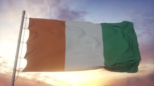 Flag of Cote D'ivoire Waving in the Wind Sky and Sun Background