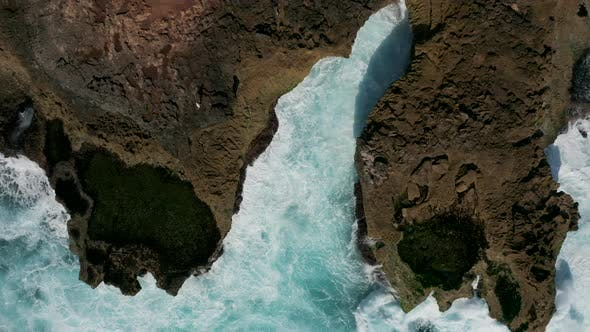 Thumbnail for Top down aerial view of waves crashing into a small rocky bay