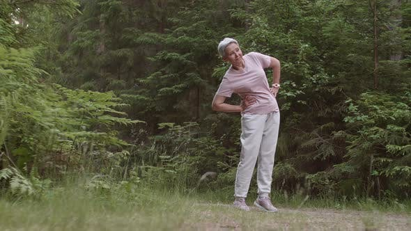 Thumbnail for Aged Sportswoman Doing Exercises in Forest