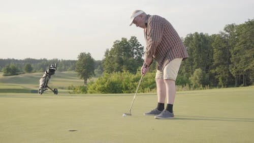 Cute Old Man Playing Golf Alone on the Golf Field
