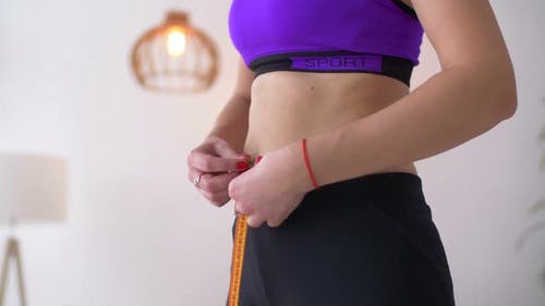 Midsection of Fit Woman Measuring Her Waist