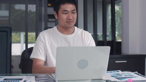 Young Asian business man records of income and expenses at home.