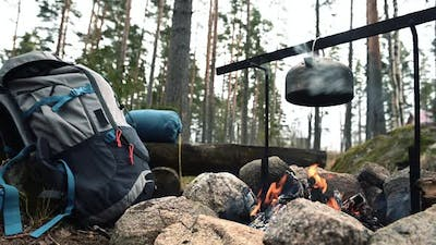 Backpack and Metal kettle on a campfire in the forest