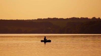 Fisherman in a boat silhouette. Mature man fishing from the boat on the pond at sunset