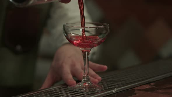 Thumbnail for Barman Pouring Red Alcohol Preparing Cosmopolitan Into Champagne Glass