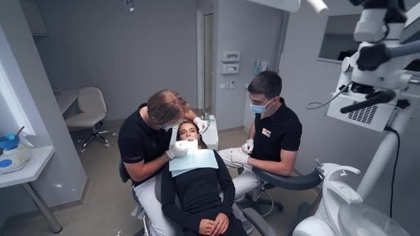 Dentist examines female's teeth. Professional stomatologist and his assistant treat patient's teeth