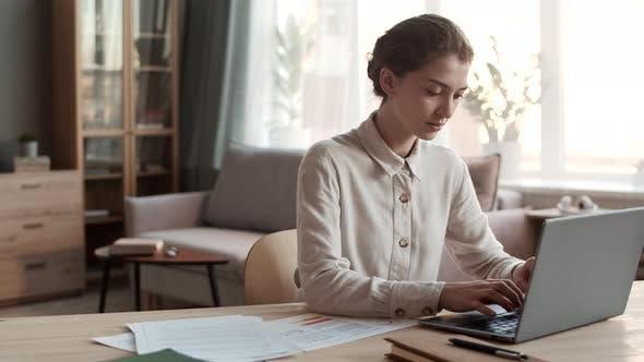 Frau arbeitet zu Hause mit Laptop
